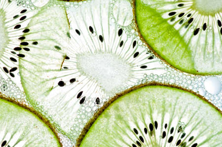 Sliced kiwi covered with bubbles in water isolated on a white background. photo