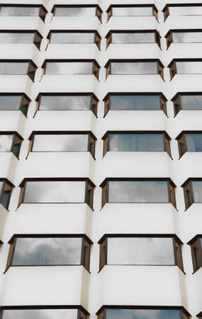 Corporate glass building, sky reflection, city background.