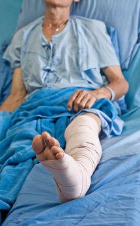herida: hombre con una herida en la pierna, acostado en la cama.