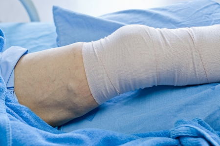 wound care: man with a leg wound, lying on the bed.