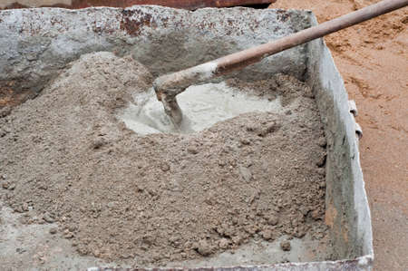 Construction worker mixing concrete with a hand mixer