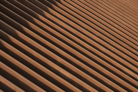 Sunlight and shadow on surface of the old artificial wooden lath in abstract diagonal pattern and perspective view for background design and architecture concept