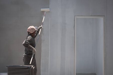 Rear side view of Asian builder worker using long handle roller brush to applying primer white paint on cement wall background inside of house construction site