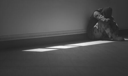 Side view of hopeless man sitting alone with hugging his knees on the floor in the corner of room in dark tone and black and white style