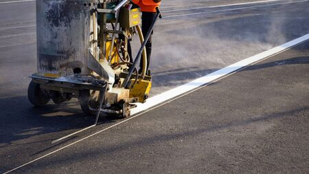 Low section of road worker with thermoplastic spray road marking machine working to paint traffic white line with steam and railway track crossing on asphalt road surface