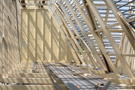 Sunlight and shadow on surface of white wooden roof truss structure with material under construction, renovation and architecture concept