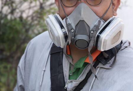 Une partie du visage humain dans un demi-masque respiratoire polyvalent avec des vêtements de protection chimique pour la sécurité et la prévention lors de la pulvérisation de produits chimiques pour éliminer les moustiques et prévenir le travail de la dengue