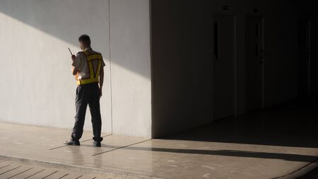 Asian security guard in safety vest walking on sidewalk of parking garage, he using walkie-talkie or portable radio transmitter with sunlight and shadow on surface of gray cement wall background