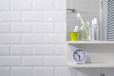 Toothbrush in glass bottle, tooth paste in little green bucket, hand sanitizer spray with clock on shelf and mirror on white tiles wall in modern bathroom, personal accessories Stock Photo