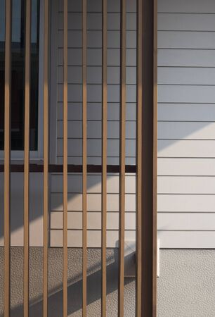 Sunlight and shadow on surface of  wooden lath in front of white artificial wood and gray  wall with part of glass window frame, cheap house materials prices in home architecture concept