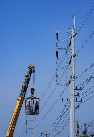 Low angle view of crane truck lifting 2 electricians in metal man basket to working on electric power pole against blue clear sky in vertical frame