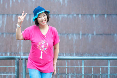 Asian happy female tourist in casual style is showing the victory gesture while smiling for the camera in front of waterfall decoration on building's wall