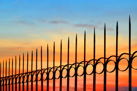 Silhouette arrow spiky metal fence against beautiful sunset sky background, side view with copy space Banco de Imagens