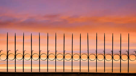 Silhouette arrow spiky metal fence against beautiful sunset sky background, front view with copy space