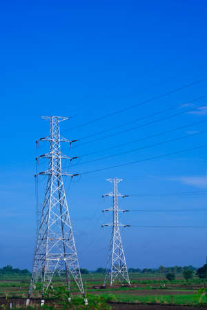 Two high voltage towers and cable lines in countryside with blue sky background in vertical frame