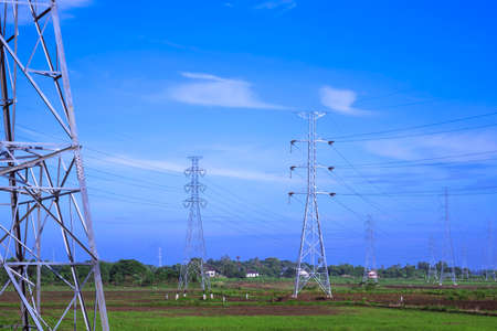 Many high voltage towers and cable lines in countryside with blue sky background