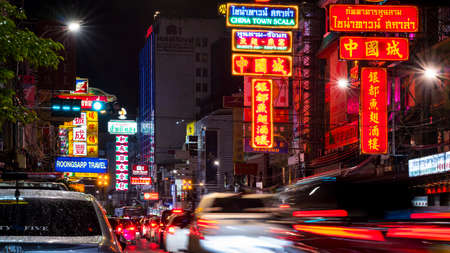Bangkok, Thailand - August 08,2020 : Motion blurred of traffic light with colorful illuminated labels and building signs on Yaowarat road in rainy night