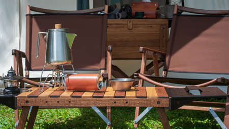 Stainless steel kettle, portable gas stove, bowl and vintage lanterns with outdoors wooden table set in front of tent on green lawn in camping area Banco de Imagens