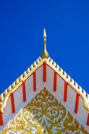 Low angle view of golden gable apex on ornamental Thai temple roof against blue clear sky background in vertical frame