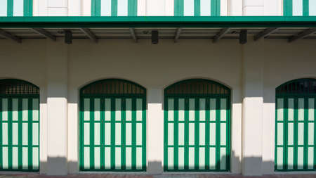 Sunlight and shadow on green wooden folding arches doors with awning on vintage white building wall