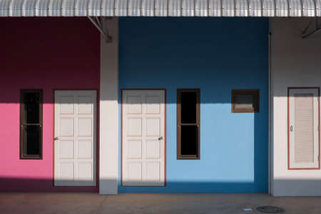 Sunlight and shadow on front doors and storage compartment surface with awning of the blue and pink apartment Standard-Bild