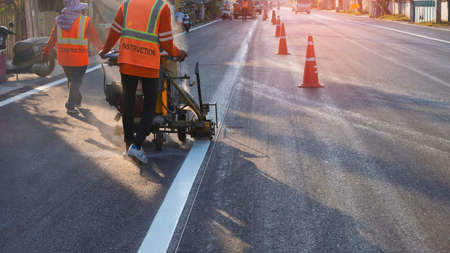 Rear view of road workers team with thermoplastic spray marking machine working to paint traffic white line on asphalt road surface with sunlight and shadow in evening time, selective focus