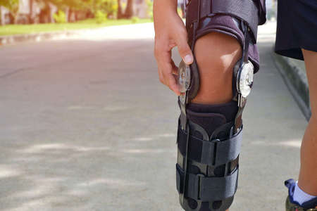 Young man's hand turns angle movement control of supportive knee brace on his leg for jogging with flare light and blurred public park background