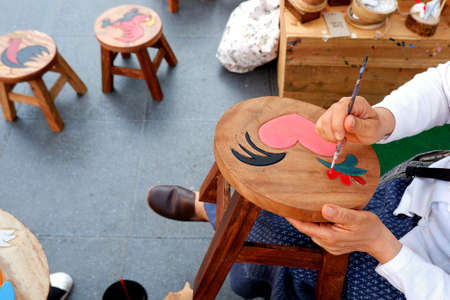 Bangkok, Thailand - February, 22,2019 : High angle view of mature Asian female hands using paint brush to drawing and painting picture on tamarind wooden chair in Thai art and culture exhibition 에디토리얼