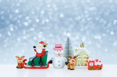 Santa Claus doll and Christmas decorations on snowing background, creative artwork Christmas and new year decoration Stock Photo