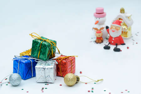 Focus at colorful gift boxes pile with blurred Santa Claus doll and Christmas decorations on white background 版權商用圖片