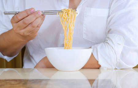 Close up man's hand in white shirt using silver chopsticks to eat instant noodles in white bowl at home