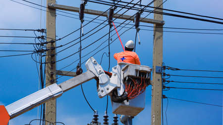 Low angle view of electrician with disconnect stick tool on crane truck are working to install electrical transmission on power pole against blue sky