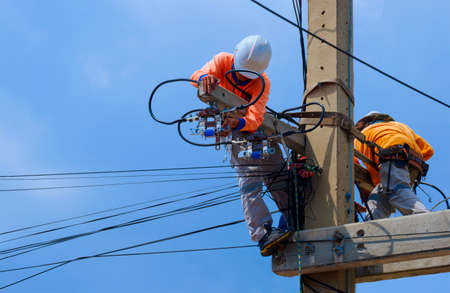 2 electricians with safety equipment are working to install electrical system on power pole against blue sky background Zdjęcie Seryjne