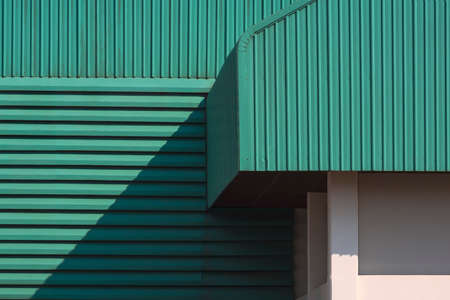 Sunlight and shadow on part of green corrugated metal roof with louver on the wall of large factory building