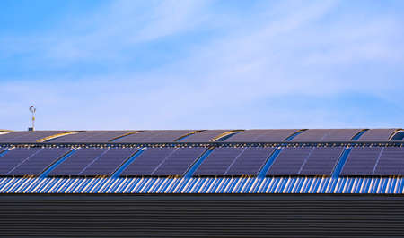 Many solar panels on curved steel roof of industrial building against blue sky background 版權商用圖片