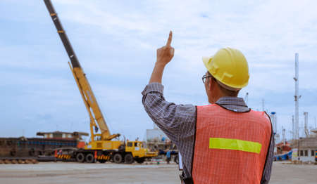 Rear view of foreman in reflective clothing with helmet showing number one hand sign gesture while controlling to transfer goods in shipping port area