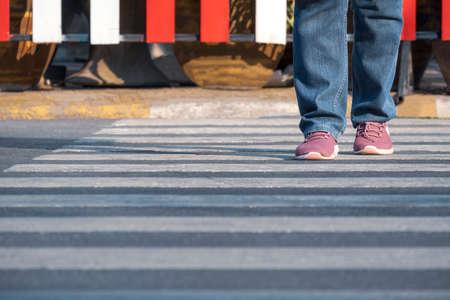 Front view of human legs walking across the street on zebra crossing in public area