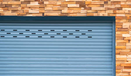 Front view of roller shutter door on timber wall background
