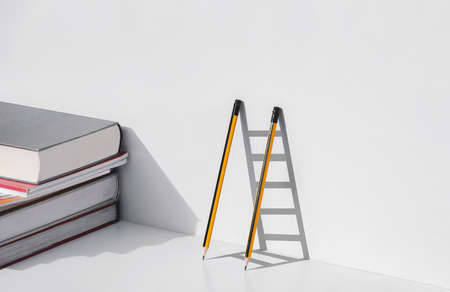 Two pencils and shadow in form of ladder with stack of textbooks on white tabletop, Education, learning is the ladder to success concept