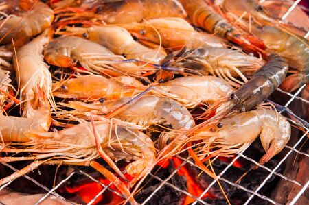 grilled prawns on flaming grill photo