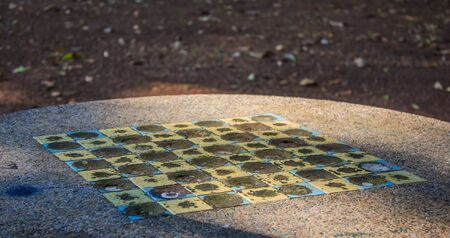 checkers: Old concrete table with mosaic - checkers game Stock Photo