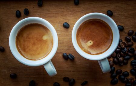seeds coffee: Two espresso coffees in small white cups,with a coffee bean resting on the wood background