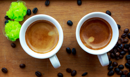 coffees: Two espresso coffees in small white cups,with a coffee bean resting on the wood background