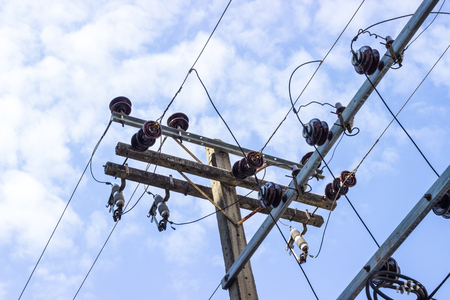against the current: Electric pole connect to the high voltage electric wires on against bright blue sky