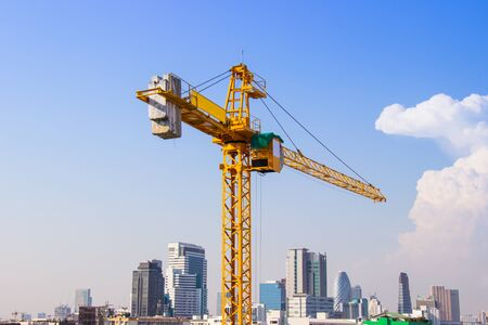 Crane is used in the construction of high buildings for tool of large industry under the blue sky and white clouds.