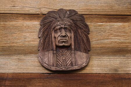 Red indian head Carved with wood hang on the brown wooden wall for interior and exterior decoration.