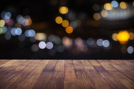 Desenfoque café restaurante o cafetería vacía de mesa de madera oscura con fondo abstracto borroso bokeh oro claro para exhibición de productos de montaje o diseño.