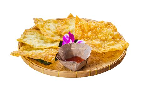 Yellow fried dumplings and a cup of sauce on a bamboo dish at decorated with orchid isolated on a white background. Standard-Bild