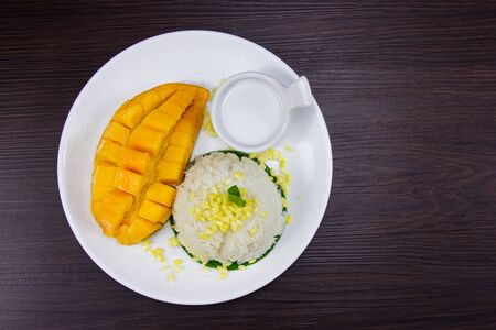 Sticky rice with fresh ripe mango with coconut milk put white plate on brown dark wooden table