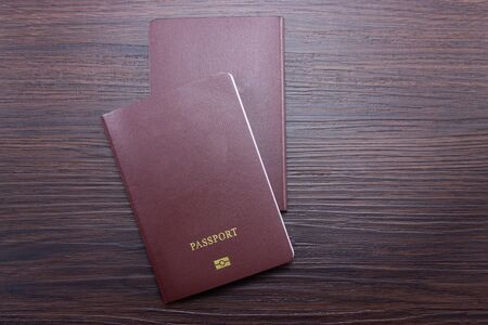 Passport on brown dark wood floor for travel and leisure. Top view.